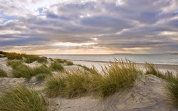 Stunning inspirational sunset image with glowing sun beams and grassy sand dunes