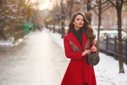 Stunning long-haired brunette woman wearing red maxi coat and holding trendy handbag stands at winter snowy street. Glamorous young female model in luxurious outerwear posing outdoors