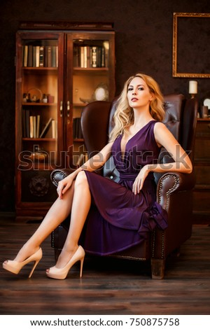 Stunning majestic domineering woman in a beautiful dress and in high-heeled shoes sits in an expensive leather chair in her home office #750875758
