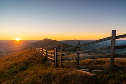Stunning Mam Tor Peak District early morning dawn sunrise with long fence and beautiful golden hour orange light sun on the horizon of Hope Valley Castleton countryside landscape