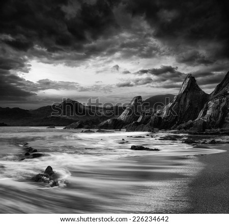 Stunning mountain and sea sunset landscape  black and white