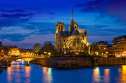Stunning Notre-Dame Cathedral (1163) and Parisian apartments along the banks of the river Seine, Paris, France illuminated at night.