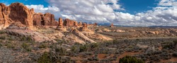 Stunning panorama of Garden of Eden sandstone rock formations on a sunny day with beautiful cloudscape, Arches National Park, Moab, Utah
