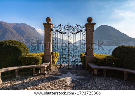 Stunning panorama view of Lugano Lake with Monte San Salvatore in background from gate of Cancello sul Lago di Lugano in Parco Ciani park on sunny autumn day, Canton of Ticino, Switzerland Zdjęcia stock ©