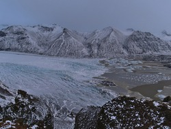 Stunning panoramic view of majestic Skaftafellsjökull, an outlet glacier of Vatnajökull in Skaftafell national park in southern Iceland with glacier lagoon and rugged snow-covered mountains in winter.