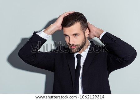 Stunning, perfect, manly, virile, harsh guy in classic outfit holding two hands on head, looking to the side with serious expression, isolated on grey background