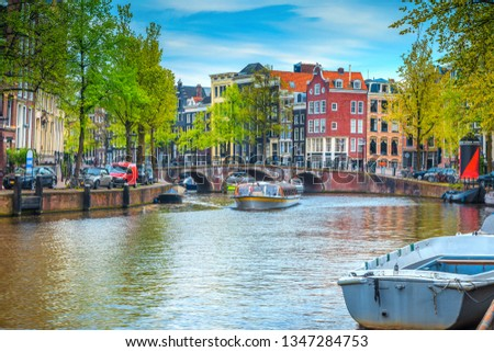 Stunning popular travel and touristic location, fabulous cityscape with traditional dutch houses. Water canal with touristical boats and bridge over the river, Amsterdam, Netherlands, Europe #1347284753