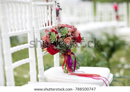 Stunning red bridal bouquet on white chair. Wedding ceremony. Mix of succulents, orchids and roses