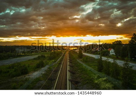 Stunning reflection of sunlight on moving cloud and leading train line to the orange horizon in beatiful summer day in a cityscape background #1435448960