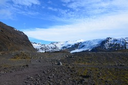 Stunning rugged volcanic landscape under cloudy blue skies.