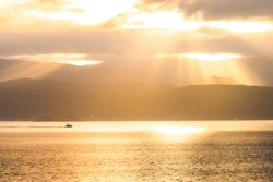 Stunning scene sunrise in the morning. Speed boat on the sea. Golden light go through the cloud to the mountain and sea.