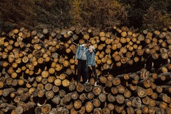 Stunning sensual outdoor photo of couple kissing and standing on the stack of firewood in the beautiful colorful autumn forest. Loving couple embracing and kissing on the felled logs in the forest.