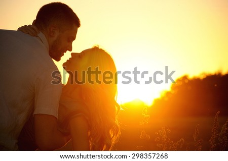 stunning sensual young couple in love posing in summer field at the sunset, happy lifestyle concept