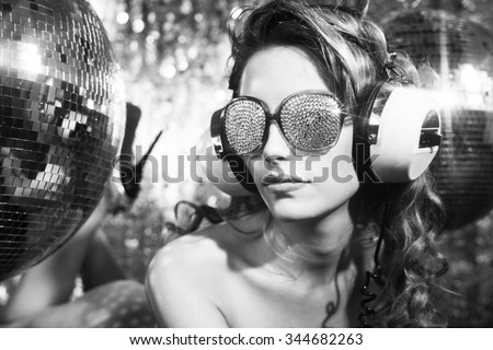 stunning sexy disco woman with crystal covered sunglasses poses on a bed, surrounded by disco balls
