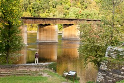 Stunning shot of a man standing on a stone wall overlooking a river next to a bridge