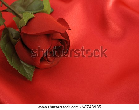 Stunning silk rose on red satin