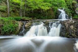 Stunning Slow falling Water Hallamolla Waterfall in lush rural Forest during springtime in Skane Osterlen near national park Stenshuvud, South Sweden.  Long Exposure Waterfall.