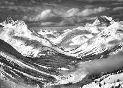 Stunning, snow covered mountain top alpine valley in black & white with large depth of field.