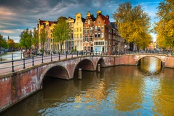 Stunning spring cityscape, Amsterdam water canals and typical dutch houses at  sunset, Netherlands, Europe