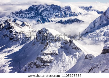 Stunning sunny winter view to peaks in moutains and clouds in Dolomites Alps, Italy #1105375739