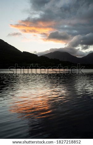 Stunning sunrise landscape image looking across Loweswater in the Lake District towards Low Fell and Grasmere with colorful sky breaking on the mountain peaks