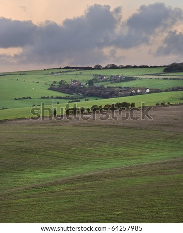 Stunning sunrise over agricultural landscape in England with dramatic stormy sky