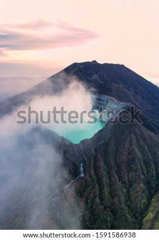 Stunning sunrise over the Ijen volcano with the beautiful turquoise-coloured acidic crater lake. The Ijen volcano complex is a group of composite volcanoes located in Banyuwangi, East Java, Indonesia.