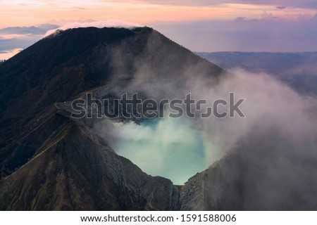 Stunning sunrise over the Ijen volcano with the beautiful turquoise-coloured acidic crater lake. The Ijen volcano complex is a group of composite volcanoes located in Banyuwang East Java, Indonesia.