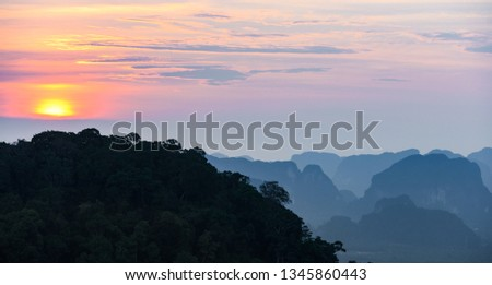 Stunning sunset behind some beautiful limestone mountains. Picture taken from the Tiger Cave Temple (Wat Tham Sua) Krabi, Thailand.
