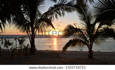 Stunning sunset framed by two palm trees silhouetted in the light on a white sandy beach trees with calm waters overlooking a coral reef on Rarotonga in the Cook Islands. #1503718721