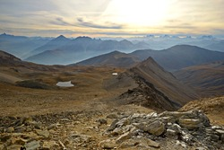 Stunning sunset from the summit of rocky and barren mountains on foggy valleys below. Little lakes reflecting sunlight. Location: western Alps, Torino Province, Italy.