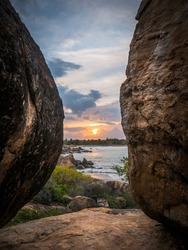 Stunning Sunset In Between Two Huge Rocks on the Beach at Whiskey Point, Arugam Bay, Sri Lanka