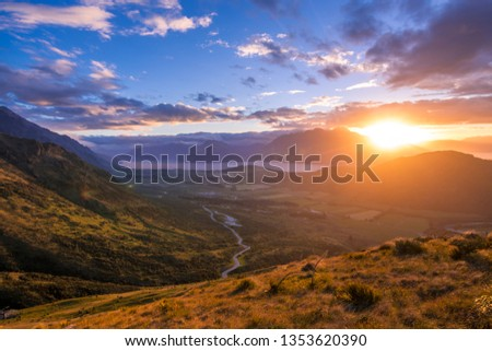stunning sunset lights shining through clouds over the mountains and lake #1353620390