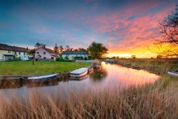 Stunning sunset over the village green and boats on the river at West Somerton in the Norfolk Broads