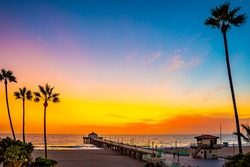 Stunning sunset sky view on Manhattan Beach Pier, California. American west coast tropical landscape with tall palm trees near the ocean.