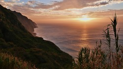 Stunning sunset with dramatic cloudy sky above wild Atlantic Ocean in the west of Madeira island, Portugal with water reflection, majestic cliffs on the coast and reed plants in foreground.