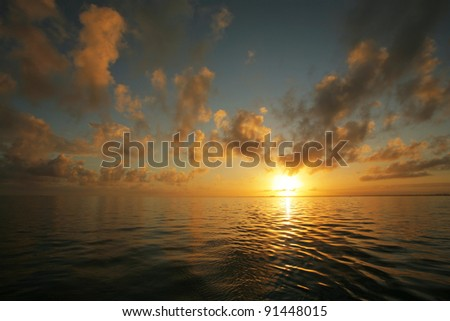 Stunning tropical sunset over glassy sea