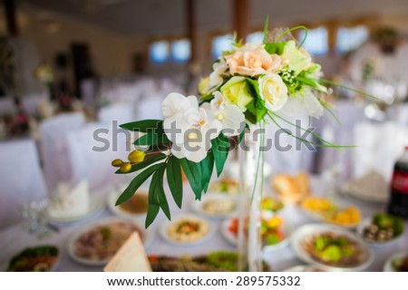 stunning unusual beautiful bouquet with orchids and roses in vase on the background of restaurant