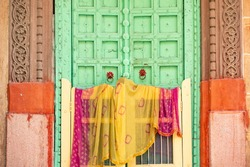 Stunning view of a traditional Indian home with a green wooden door and colorful traditional Indian clothes (Sari) hanging to dry. Blue City of Jodhpur, Rajasthan, India.