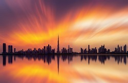 Stunning view of Dubai skyline  with warm Pastel Sunset Clouds and reflection