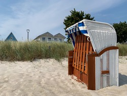 Stunning view of green grass on sandy dunes cland Baltic sea beach landscape with traditional beach chair strandkorb in Scharbeutz Germany