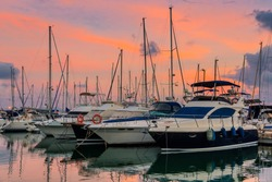 Stunning view of luxury yachts at the pier against the sunset. Yachts and boats anchored in marina.