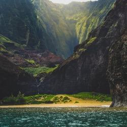 Stunning view of secluded Kalalau Beach and Kalalau Valley from a boat on a sunny day, Na Pali Coast, Kauai, Hawaii