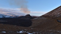 Stunning view of smoking erupted volcano in rocky Geldingadalir valley near Fagradalsfjall mountain, Grindavík, Reykjanes peninsula, southwest Iceland with people hiking to eruption site.