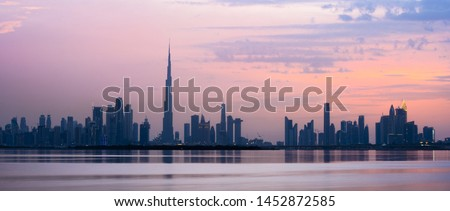 Stunning view of the Dubai skyline silhouette during sunset in the background and silky smooth water flowing in the foreground. Dubai, United Arab Emirates.