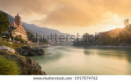 Stunning view of the Ganga river embankment with the Lakshman Jhula bridge and Tera Manzil Temple (Trimbakeshwar) during a beautiful sunset. Rishikesh, Uttarakhand, India. Stock fotó ©