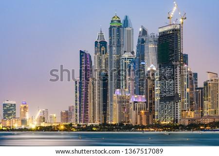 Stunning view of the illuminated Dubai Marina skyline during sunset. Picture taken from the  Palm Jumeirah artificial archipelago. Dubai Marina, Dubai, United Arab Emirates.