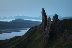Stunning view of the large pinnacle rock towering over a lake and the sea before dawn. The Old Man of Storr, The Isle of Skye, Scotland, UK