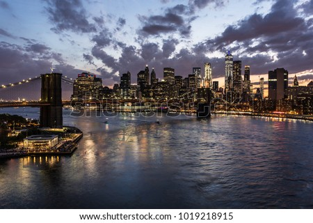 Stunning view of the nightfall over the Manhattan financial district and the Brooklyn bridge and the East river in New York city from the Manhattan bridge in the USA. #1019218915