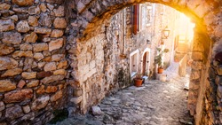 Stunning view of the street in old town of Ulcinj on sunset. Pots with flowers standing on paved pavement along stone wall. The sun light on stone arch. Travel Montenegro